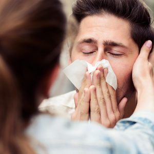 A kind woman looking after her suffering boyfriend as he blows his nose.